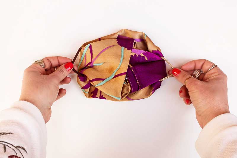 Gently pull the hair ties, place over your ears, adjust on your face making sure the mask fits firmly over your nose and under your chin. Voilà! A quick DIY no-sew face mask in less than a minute.